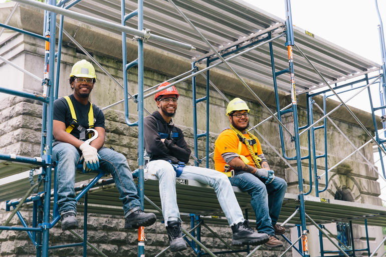 Trainees from the 2017 program take a rest on the scaffolding at Woodlawn Cemetery.
