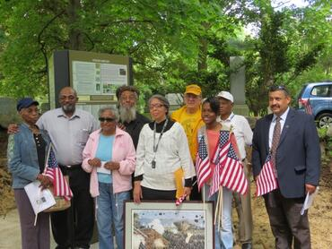 Group shot at a Memorial Day ceremony dedicated to the unveiling of a three-sided graphic kiosk, 2014.