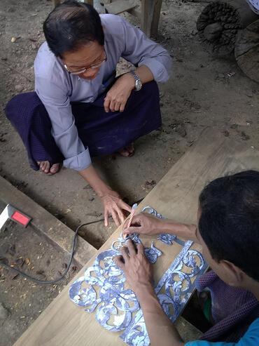U Kan Khyun helps a woodcarver plan a carving.